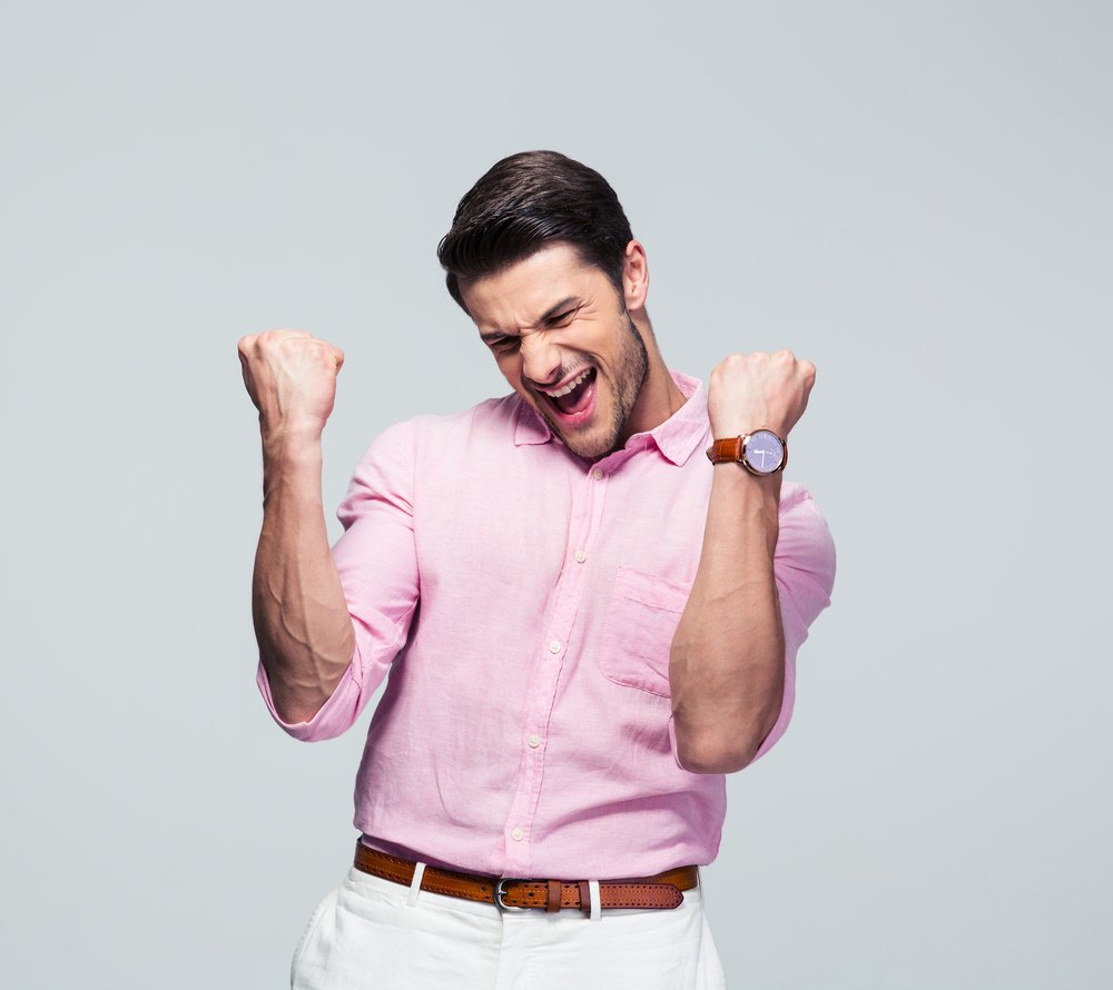 Happy young man celebrating his success over gray background